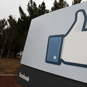 """Image: A sign with the """"like"""" symbol stands in front of the Facebook headquarters"""