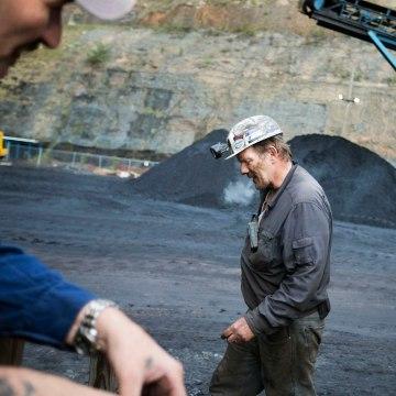 Image: Foreman John Dillon walks past piles of coal