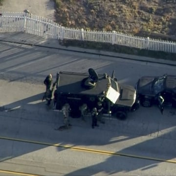 Image: Police armored cars close in on a suspect vehicle following a shooting incident in San Bernardino, California in this still image taken from video