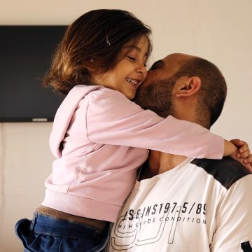 Image: Abdul Halim al-Attar, kisses his daughter Reem, 4, at their house in Lebanon.
