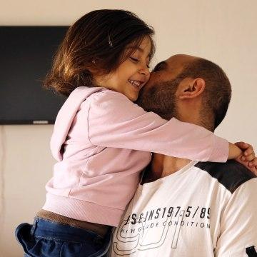 Image: Abdul Halim al-Attar, kisses his daughter Reem, 4, at their house in Lebanon.