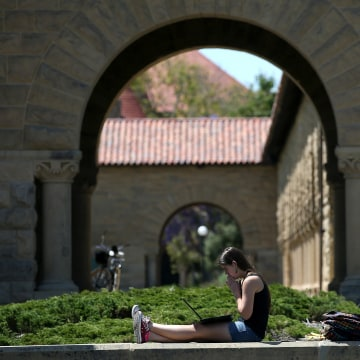 Image: A woman works on a laptop on the Stanford University campus