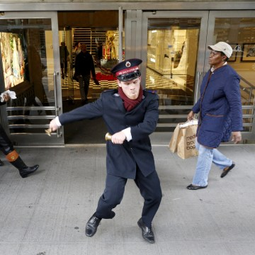 Image: Salvation Army Bell Ringer Nate Hinzman dances for Black Friday shoppers outside Bloomingdales department in the Manhattan borough of New York