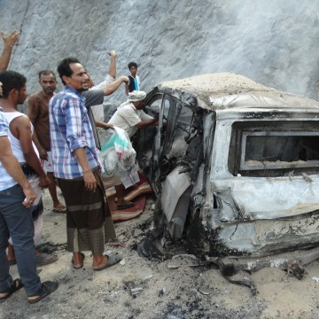 Image: Yemenis inspect the scene of a car bomb attack