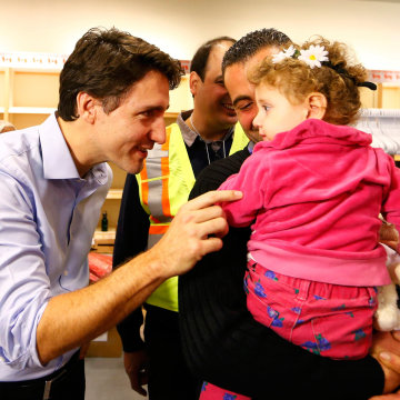 Image: Syrian refugees are greeted by Canada's Prime Minister Justin Trudeau