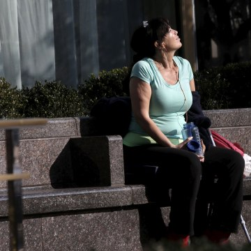 Image: A woman soaks up the sun as she sits outside in Midtown Manhattan in New York City