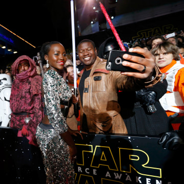 """Image: Actress Lupita Nyong'o poses with a fan as she arrives at the premiere of """"Star Wars: The Force Awakens"""" in Hollywood"""