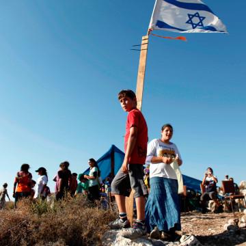 Image: Jewish settler youths gather on a hilltop near the West Bank settlement of Avnei Hefetz