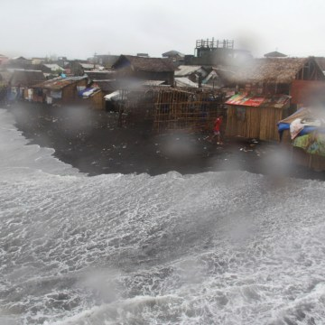Image: Residents are seen in a coastal area battered by strong winds and heavy rains brought by typhoon Melor in Legazpi city, central Philippines