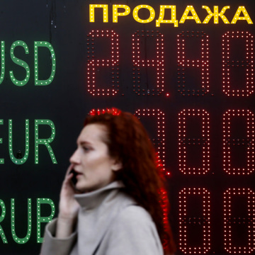Image: Woman walks past board showing currency exchange rates in central Kiev