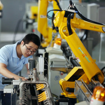 Image: Factory worker tests robot arms at factory in Jiaxing, China