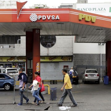 Image: People walk past a gas station of Venezuela's oil company PDVSA in Caracas