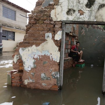 Image: A man sits near houses partially submerged in flood waters in Asuncion