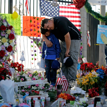 Image:A man and his son pay their respects at a makeshift memorial site