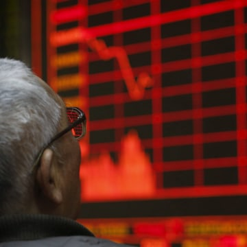 Image: A man looks at an electronic board showing stock information at a brokerage house in Beijing