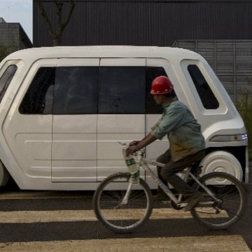 Image: Worker rides bike past driverless vehicle