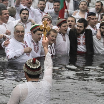 Image: A man holds the holy cross as Bulgarians sing and dance