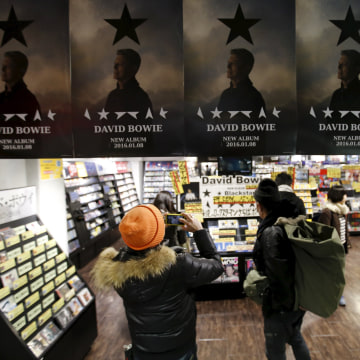 """Image: A Japanese fan takes a photo of posters depicting British rock star David Bowie's last album """"Blackstar"""" displayed at a music retailer in Tokyo"""