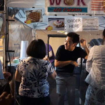 Image: A worker staffs a food booth at the Little Saigon Night Market at the Asian Garden Mall in Westminster, Calif.