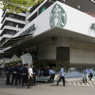 Image: Workers clean debris outside a Starbucks cafe, near the site of a militant attack, in Jakarta