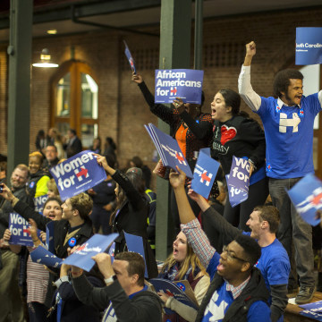 Image: Supporters wave signs and shout while they wait for Democratic presidential candidate Hillary Rodham Clinton