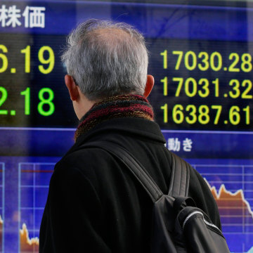 Image:  A pedestrian watches a display showing closing information of Tokyo's Nikkei Stock average