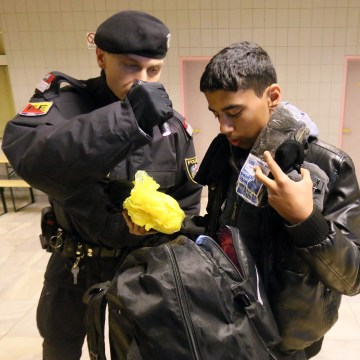 Image: An Austrian police officer checks a migrant arriving from Slovenia.
