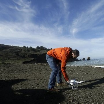 Image: Trent Lukaczyk sets up drone to take photos and videos over coastline in Pacifica, Calif.