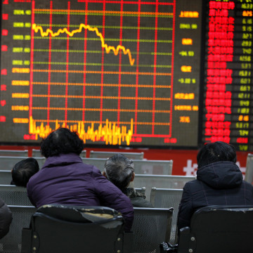 Image: Concerned Chinese investors look at a stock index and prices of shares at a stock brokerage house