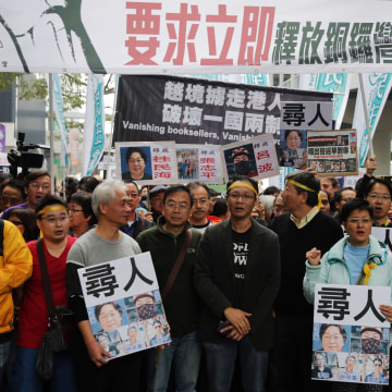 Image:People hold posters showing some of the missing booksellers from Hong Kong's Mighty Current publishing house