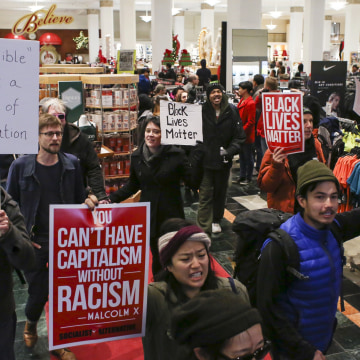 Image: Black Lives Matter protesters walk through a Macy's store on Black Friday in Seattle, Washington