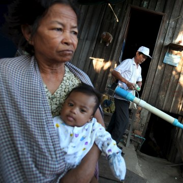 Image: A woman carries her grandson as a health official collects mosquitos and larva at her home to check for Zika virus at a village in Phnom Penh, Cambodia