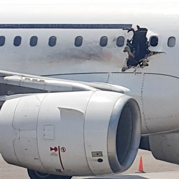 Image: A hole is seen in a plane operated by Daallo Airlines as it sits on the runway of the airport