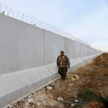 Image: A Kurdish People's Protection Units (YPG) fighter walks near a wall