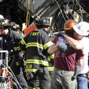 Image: Construction workers embrace as rescue crews work at the scene of a crane collapse