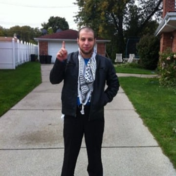 Image: Khalil Abu-Rayyan stands in his Dearborn Heights, Mich. driveway with his index finger raised.