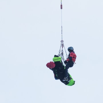 Image: Rescue teams airlift the bodies by helicopter of a group of people buried by an avalanche