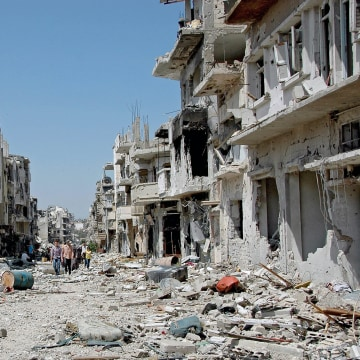 Image: Syrian civilians return to their homes in Homs