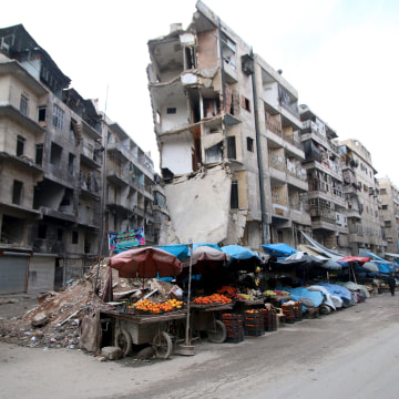 Image: Stalls are seen on a street beside damaged buildings in the rebel held al-Shaar neighborhood of Aleppo