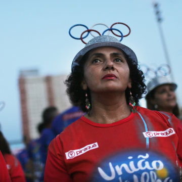 Image: Women with the Uniao da Ilha do Governador samba school wear Olympic ring hats during a pre-Carnival rehearsal
