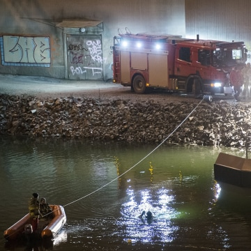 Image:  Divers and rescuers search for the victims of a deadly car crash in the canal under the E4 highway bridge in Sodertalje
