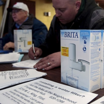 Image: Water faucet filters are distributed to Flint residents at a distribution center in a fire station in Flint