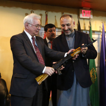 Image: Russia's Ambassador to Kabul Alexander Mantytskiy hands an AK-47 to Afghan National Security Adviser Mohammad Hanif Atmar