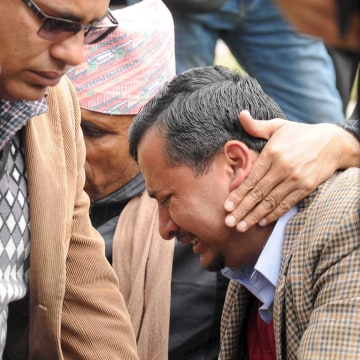 Image: A family member cries as he waits at the airport after a Twin Otter plane, operated by private Tara Air, crashed in bad weather, in Pokhara
