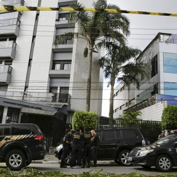 Image: Federal police officers stand in front of the apartment building that former Brazilian President Luiz Inacio Lula da Silva lived in Sao Bernardo do Campo