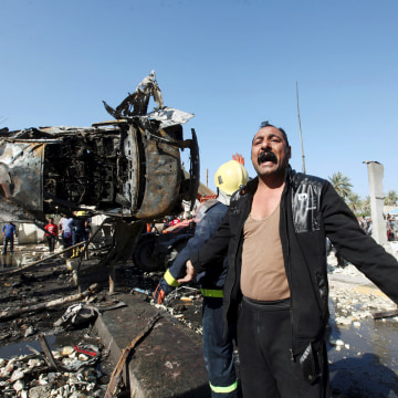 Image: A man reacts at the site of a bomb attack at a checkpoint in the city of Hilla