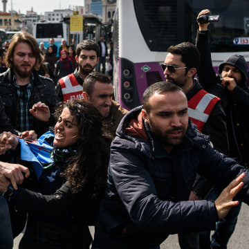 Image: Turkish plain clothes police officers try to detain a woman