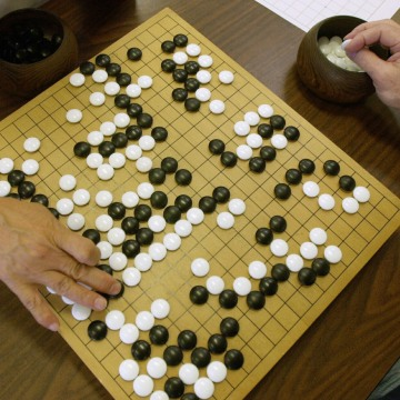 Image: A player places a black stone while his opponent waits to place a white one as they play Go