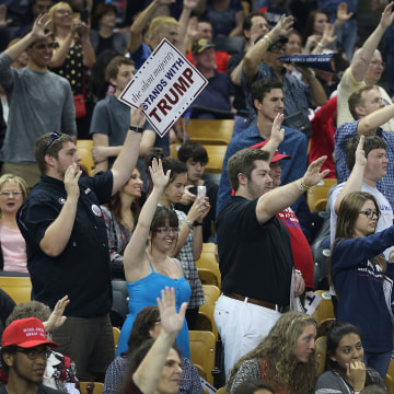 Image: Donald Trump supporters raise their arms to pledge support for the candidate