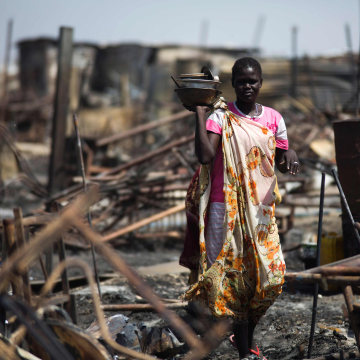 Image: A displaced women residing in the United Nations Protection of Civilians (PoC) site in Malakal, examines a burnt and looted area